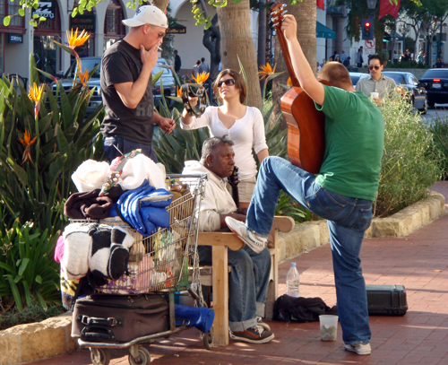 Young musicians help a homeless man collect money in State Street